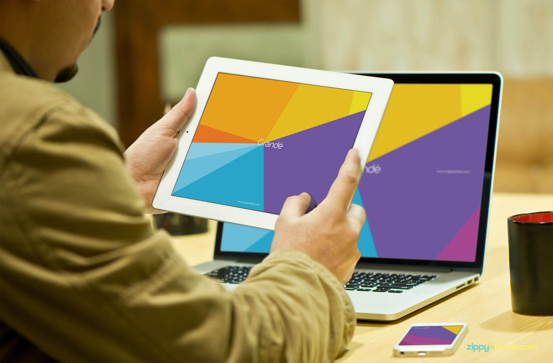 Device Mockup of a Person holding iPad and Macbook Pro in Background