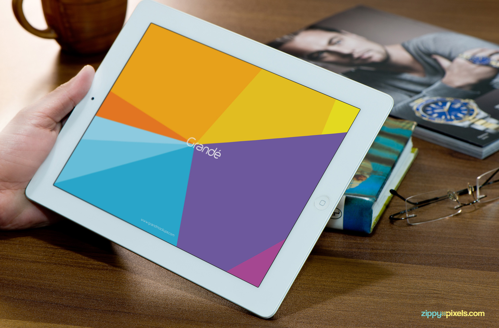 Free iPad Mockup of iPad held in hand with books in backgournd