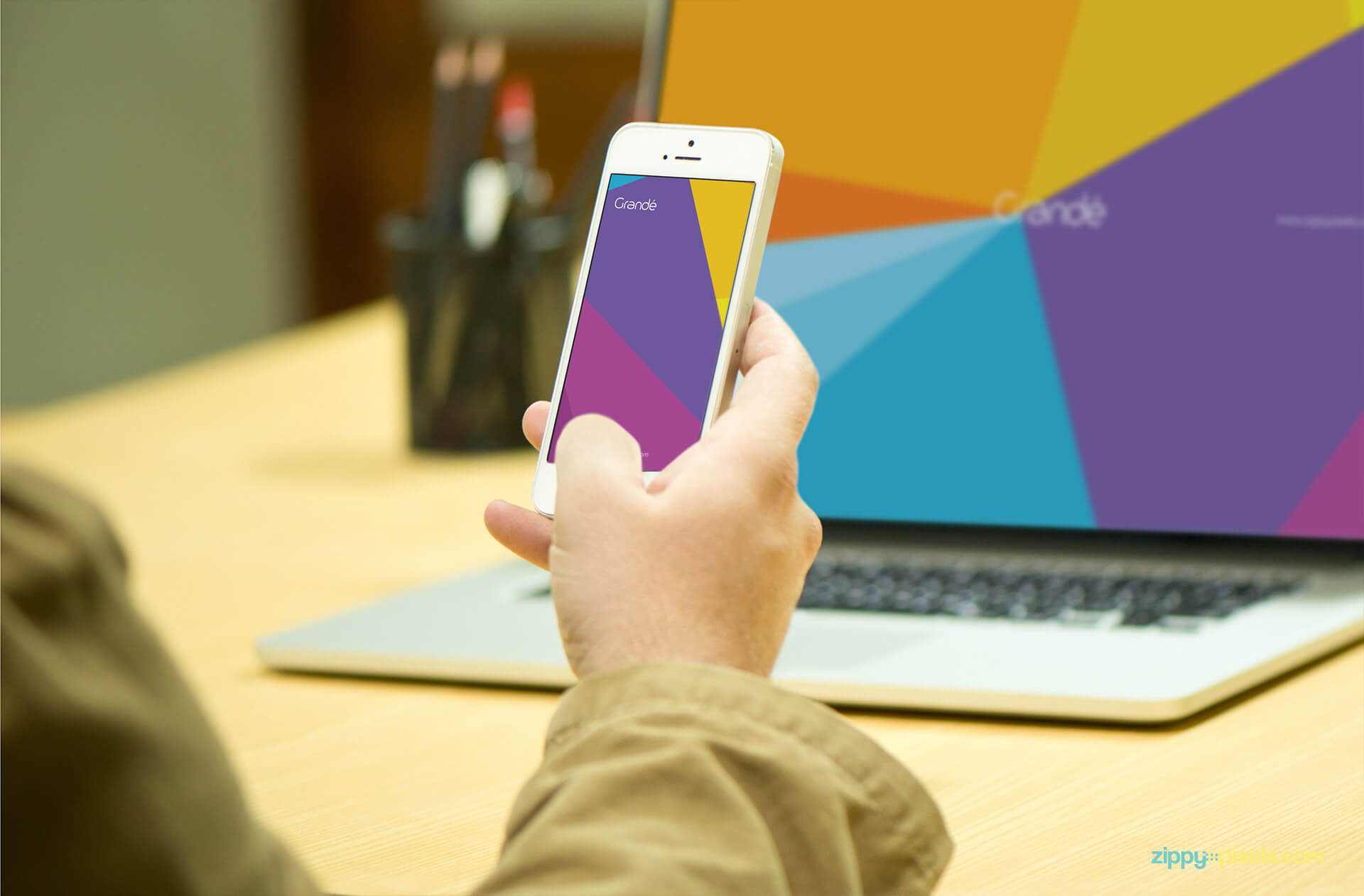 Device Mockup of iPhone Held in a Hand with a Macbook Pro in Background