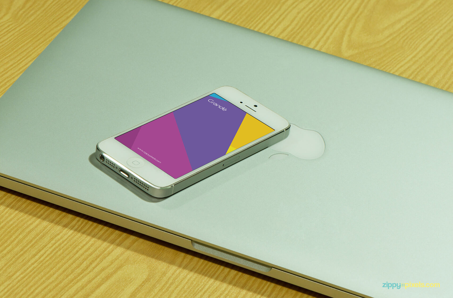 Device Branding Mockup of iPhone lying on a Closed Macbook Pro