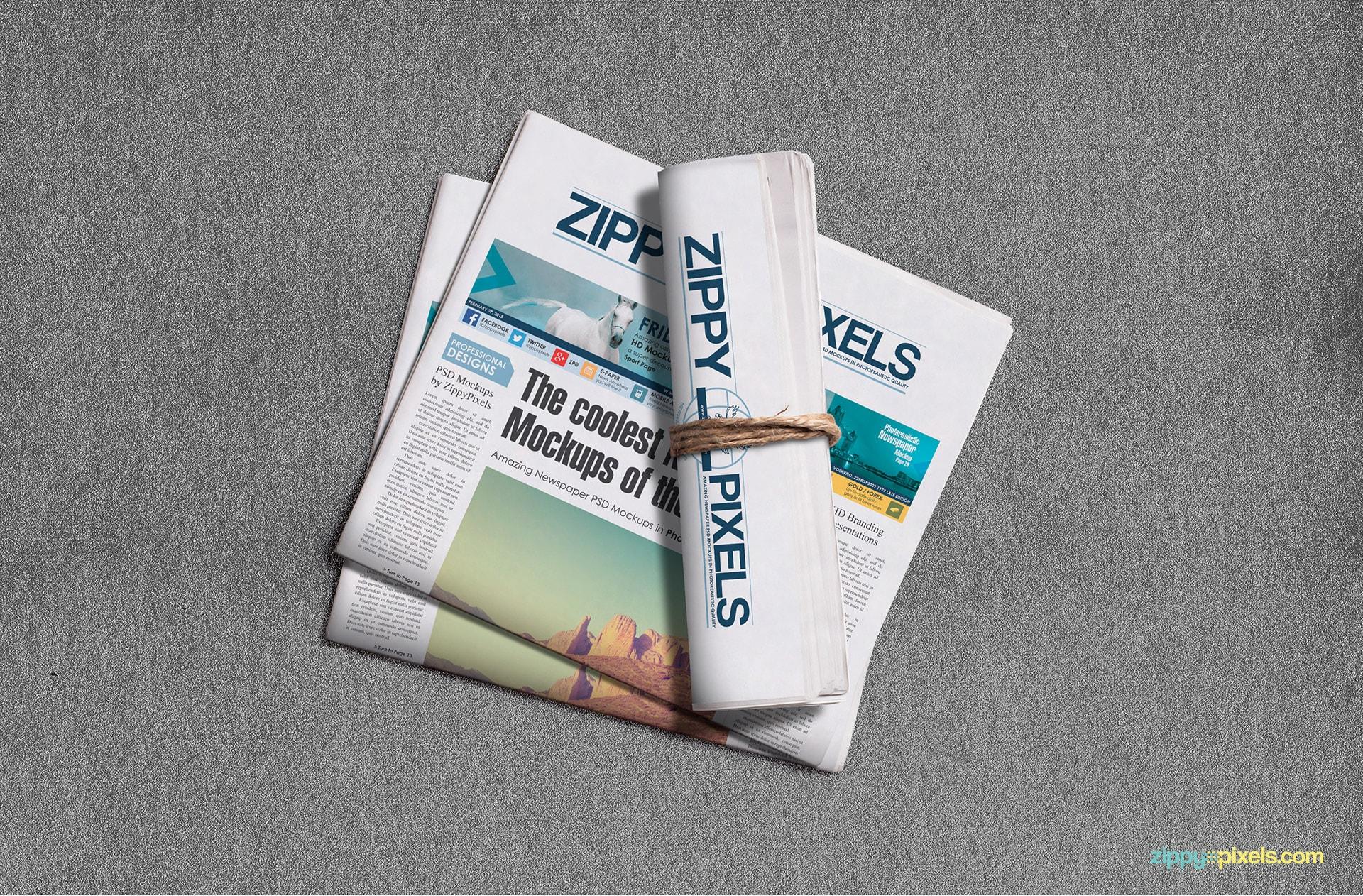 Newspaper roll lying on two half-fold broadsheet newspapers