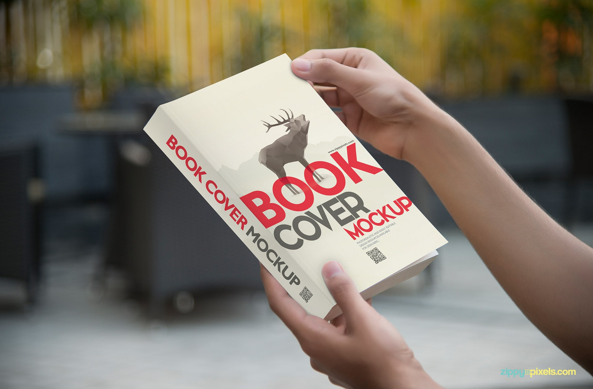 Mockup of softcover book held in hands showing front cover in a closeup