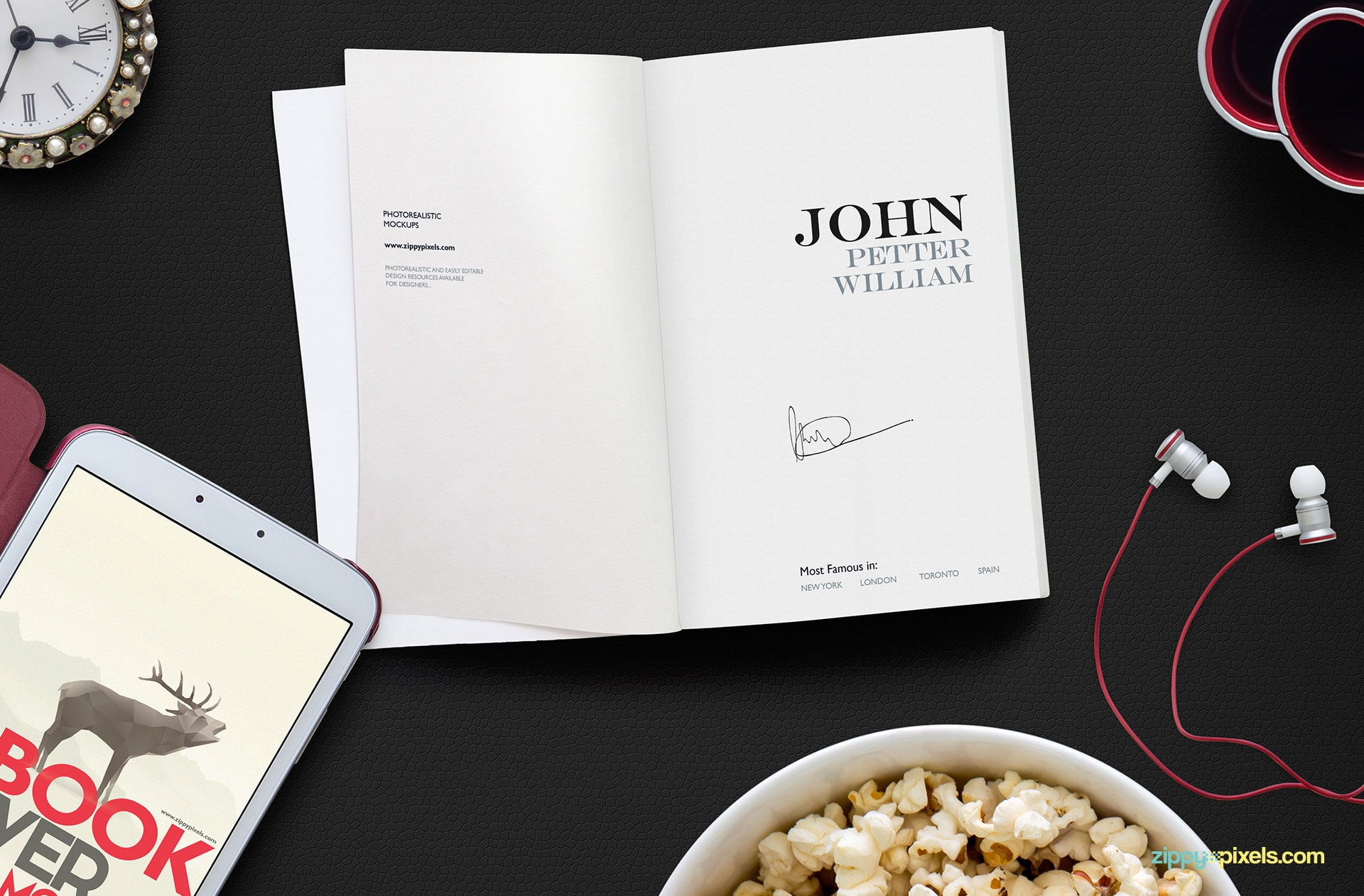 "Opened book mockup psd showing a top down view of book title page, 10.1"" tablet, bowl of pop corns, ear phones, pen holder & table clock"
