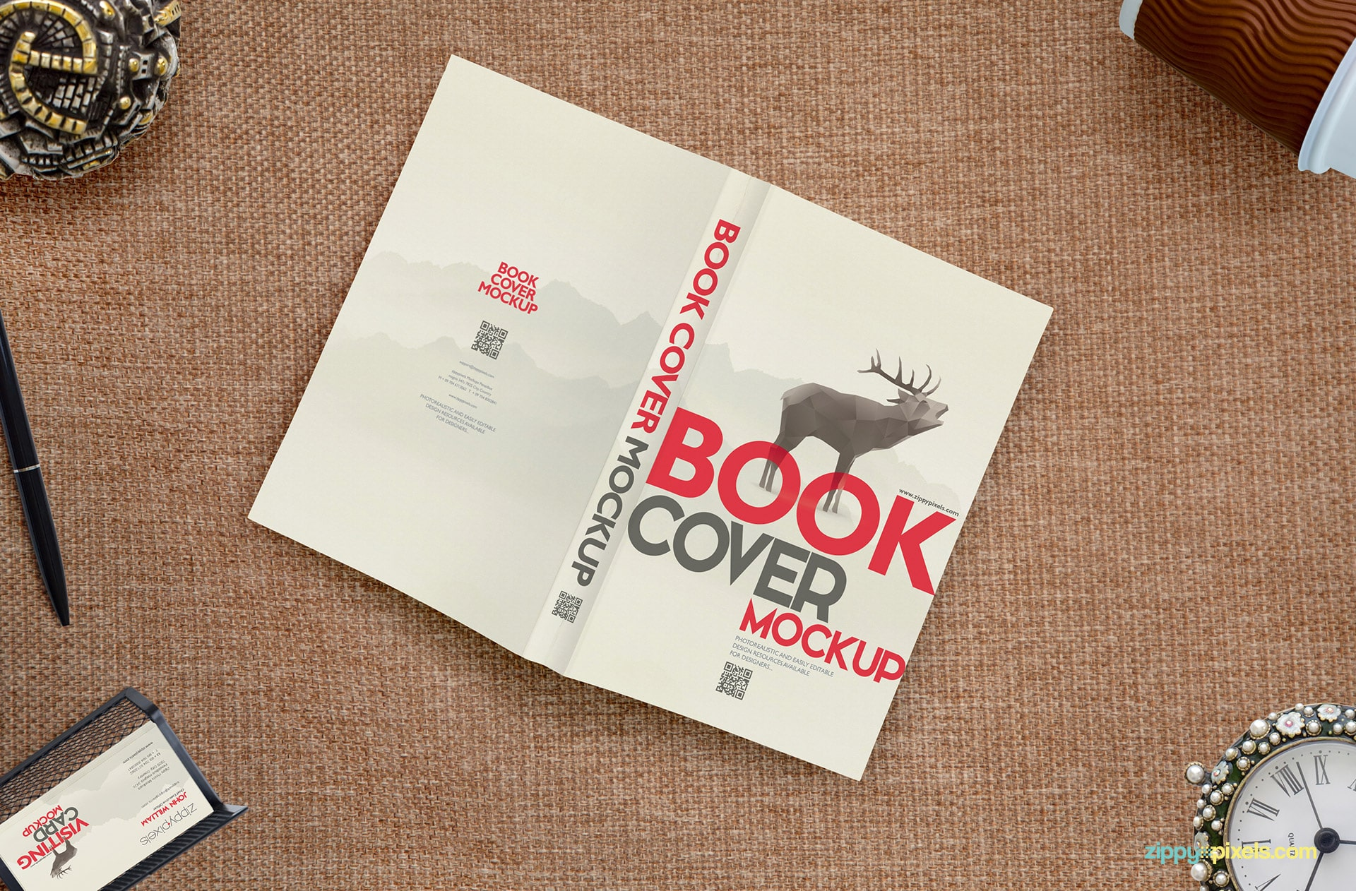 Full book cover mockup showing a book lying face down with coffee cup, business card holder, desk clock, jewelry box & ball pen