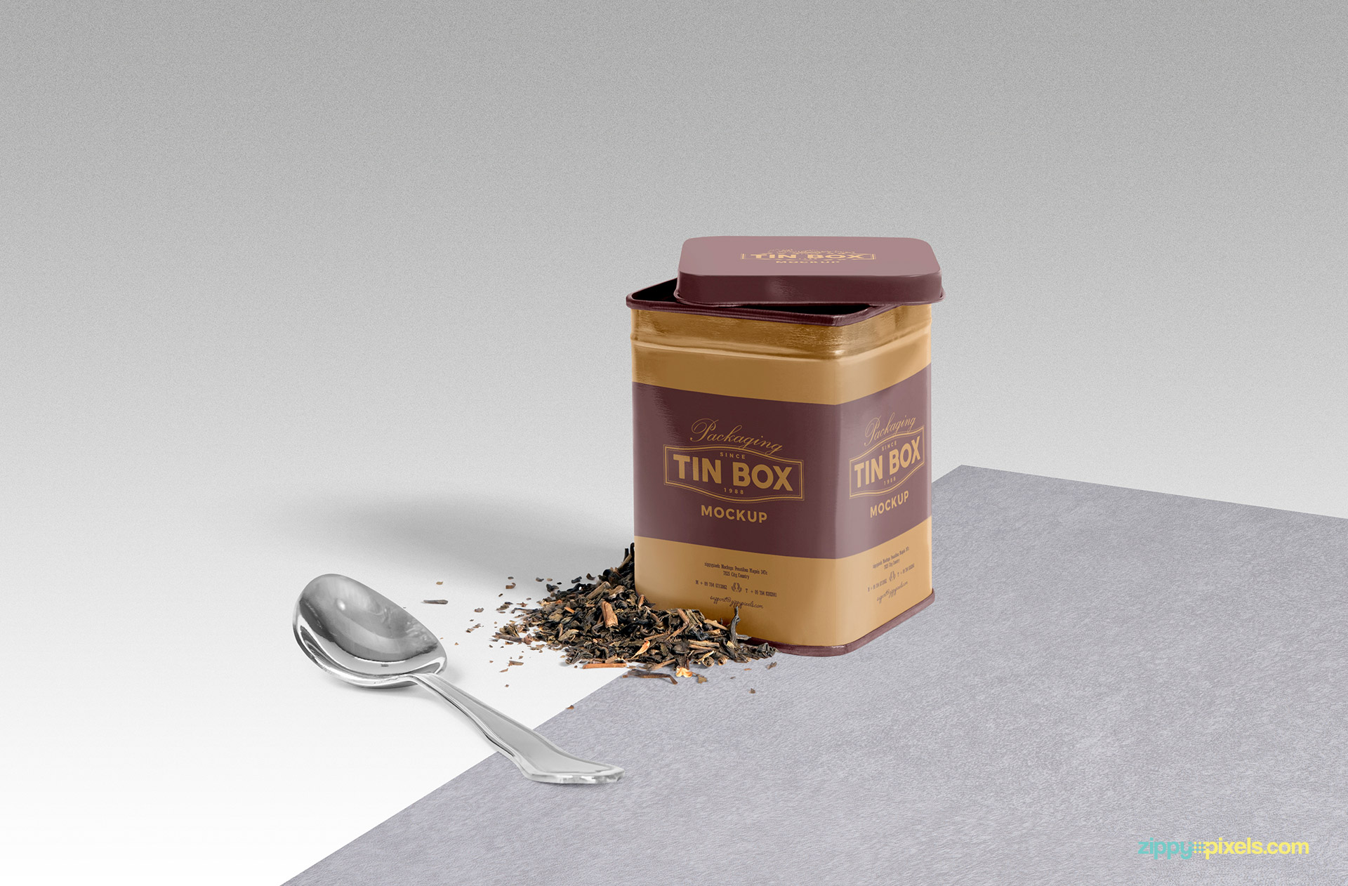 Vintage style tin box mockup with spoon and tea leaves on surface